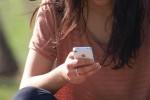 Junge Frau schreibt Textnachricht mit dem iPhone
