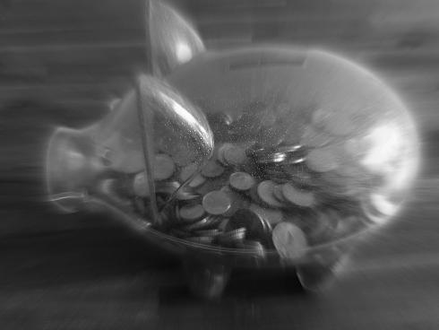 Sparschwein zur Hälfte mit Münzen gefüllt
