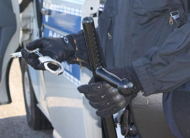 Polizist mit Handschuhen und Handschellen in der Hand