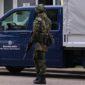 Soldat mit Waffe vor einem Bundeswehr-LKW mit der Aufschrift Wir. dienen. Deutschland.