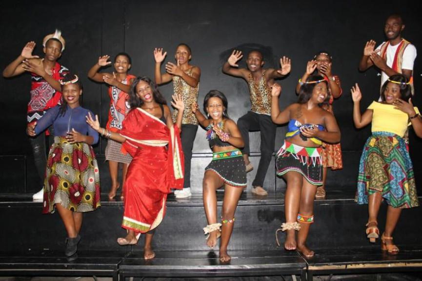 Tänzer und Sänger des UniZulu Choir in bunten Kleidern auf der Bühne