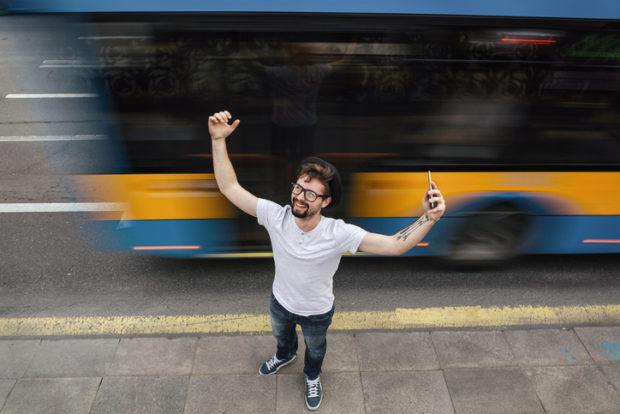 Junger Mann mit Handy in Siegerpose