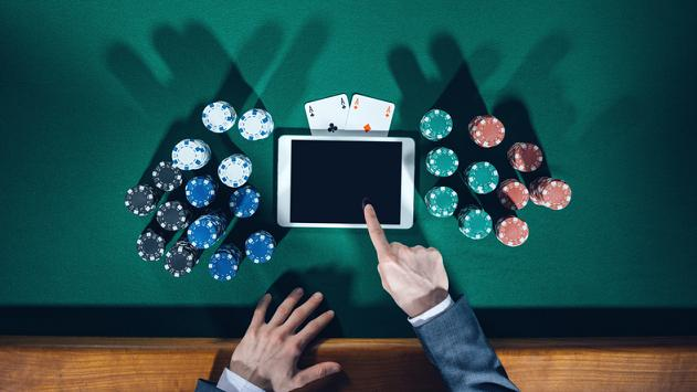 Poker player's hands with digital tablet, stacks of chips and cards on green table, top view