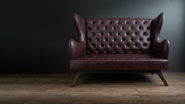 Sofa of black leather standing in center on concrete floor against dark grey wall with copy space. Vintage brown leather sofa with grunge gray wall living room.
