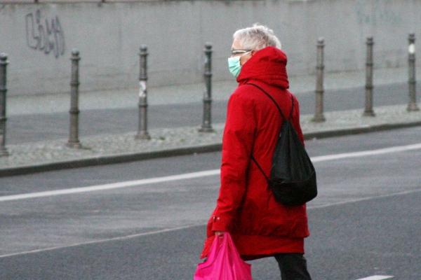 Seniorin mit Mundschutz und Einkaufstüte