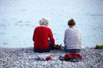 Alte und junge Frau sitzen am Strand